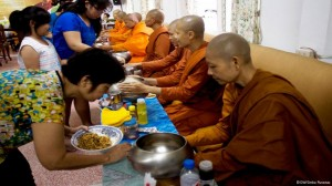 Residents offer food as alms to the monastery