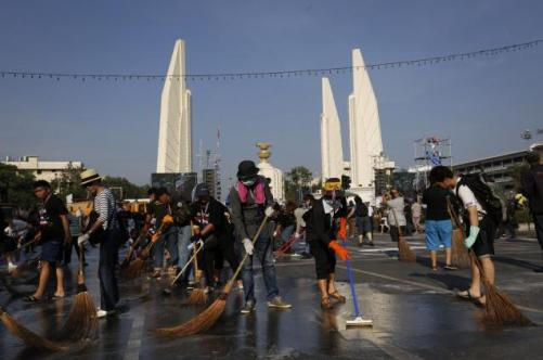 Anti-government protesters sweep streets in front of the Democracy Monument in Bangkok on Wednesday