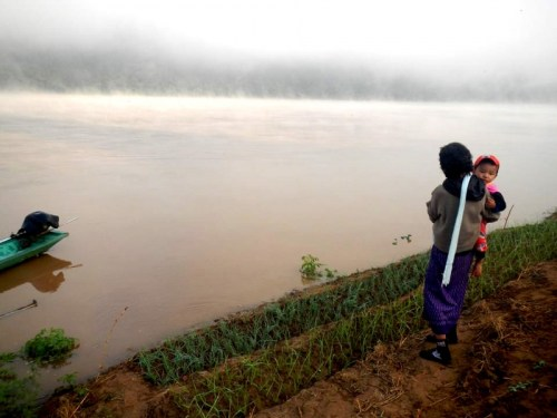 A grandma is looking at her dry-season riverbank garden as it is flooded by the Mekong, Chiang Khan, Loei (Thai-Lao border)