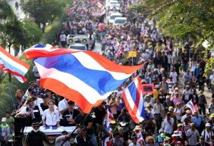 Thai anti-government protesters march during a rally on a street outside the prime minister's office of government house in Bangkok