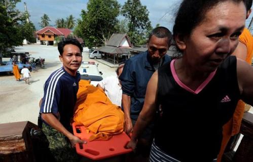 Villagers help carry the body of a 68-year old Buddhist monk who was slain by suspect gunmen at Mae Lan district of Pattani province, southern Thailand
