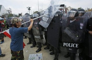 An anti-government protester strikes back at riot police retaking a protest site in Bangkok