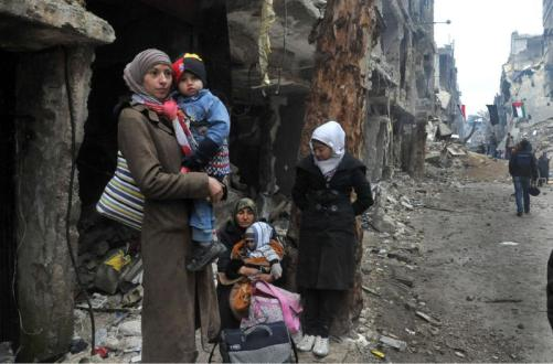 Residents of the besieged Yarmouk Palestinian refugee camp wait to leave the camp, on the southern edge of the Syrian capital
