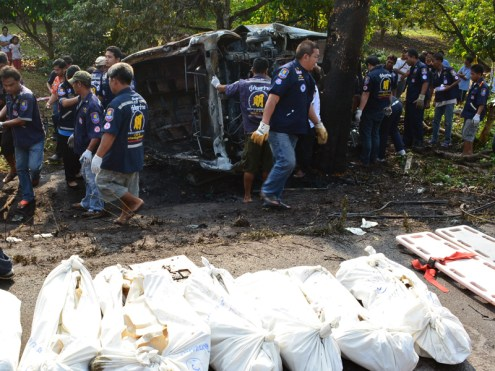 Thai rescue workers carry bodies of Cambodian migrant workers killed in a road accident in Chanthaburi province on April 11, 2014. Nine Cambodians were killed when a mini-bus carrying migrant workers returning home for the Buddhist New Year crashed and burst into flames in eastern Thailand, police said.