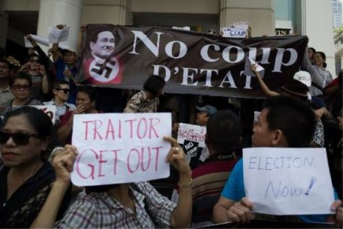 Anti coup protesters show a banner opposing Thai army chief General Prayut Chan-O-Cha during a gathering in Bangkok
