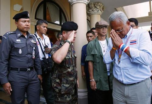 Anti-government protest leader Suthep Thaugsuban (right) greets a Thai army officer on the way out of Government House in Bangkok