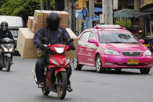A delivery motorcycle and taxi cab on the streets of Bangkok on July 1, more than a month after a Thai military junta took control of country.