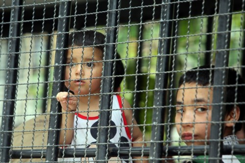 Children, part of a group of asylum seekers, sit in a truck as Thai immigration officials escort them to a court in Songkhla, southern Thailand,