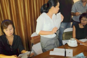 Pawinee Chumsri, Thai Lawyers for Human Rights, (center) displays for photographers her copy of the letter received from police.