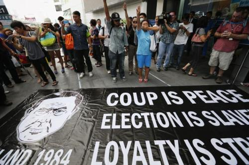 Anti-coup protesters gesture three-finger signs next to a banner with a drawing of the army chief and coup leader General Prayuth Chan-ocha as reporters take pictures outside a shopping mall in Bangkok June 1, 2014. reuters/Damir Sagolj