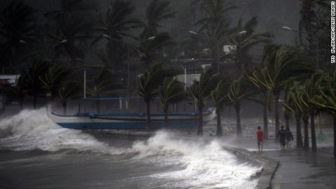 Residents walk past high waves brought about by strong winds as it pound the seawall, hours before Typhoon Hagupit passes near the city of Legazp