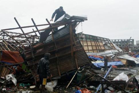 A man is seen on top of his damaged house in Tacloban, central Philippines on Dec 7, 2014. Typhoon Hagupit tore apart homes and sent waves crashing through coastal communities across the eastern Philippines on Dec 7.