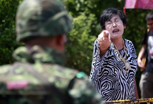A pro-government demonstrator points at a soldier during the cleanup of a protest site