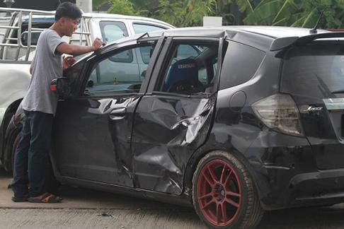 Police inspect a Honda Jazz that killed one cyclist and injured two others on Ratchada-Ram Intra Road, in front of the Bangkok Boulevard housing estate, at 10pm Monday. (Photo by Thanarak Khunton)