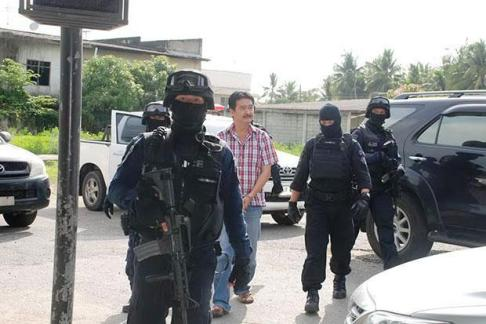 officers take Mr Banjong, who turned himself in to police on Friday, to search his house on May 9. Please credit and share this article with others using this link:http://www.bangkokpost.com/news/general/556235/alleged-trafficking-kingpin-properties-searched. View our policies at http://goo.gl/9HgTd and http://goo.gl/ou6Ip. © Post Publishing PCL. All rights reserved.