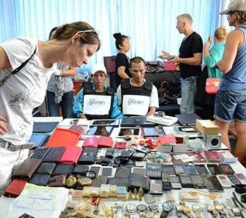 A woman looks for her belongings among the haul of stolen goods at the Hua Hin police station on Saturday as suspects Thawalchai Thawilsuk and Surintra Khumsup look on. (Photo by Chaiwat Satyaem)