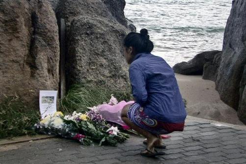 A villager laying flowers during a memorial service for two murdered British tourists