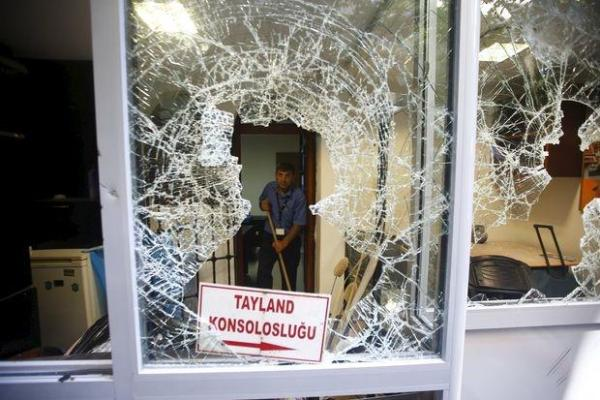 A man removes broken glass from a window of the Thai consulate damaged by protesters in Istanbul