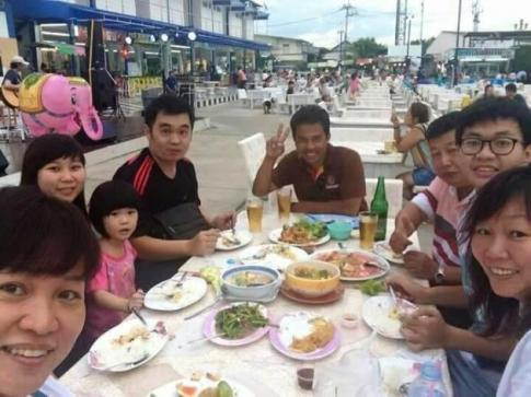 Hock Guan, 3d from right, having lunch with his family at a roadside restaurant in Bangkok. From left: Jessee, Ee Ling,. Ee Ling and Lee's daughter, Lee, their local guide, Jia Jun and Saw Gek