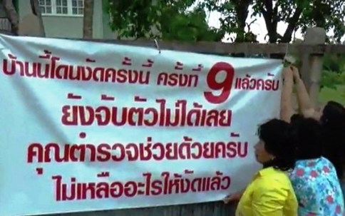 "A cloth banner with a message ""This house is robbed for the ninth time and thieves are still at large. We are begging police for help. There is nothing left for (thieves) to break in'' is put up in front of a house in Ayutthaya's Maha Rat district. (Photo by Sunthon Pongpao)"