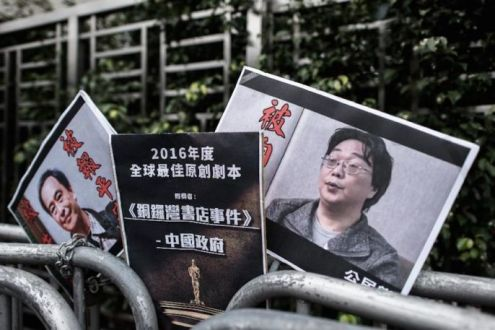 Photos of missing bookseller Lee Bo (L) and his associate Gui Minhai (R) are seen left by members of the Civic party outside the China liaison office in Hong Kong.