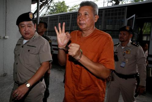 Tom Dundee, gave waiting media the thumbs-up as he arrived at court on Wednesday, wearing an orange prison uniform.