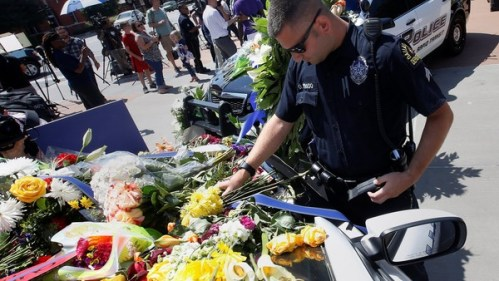 A Dallas police officer observes a moment of silence after putting flowers on a police car