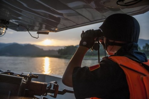 A Chinese patrolman looks through a telescope during a joint patrol by China, Myanmar, Thailand and Laos on the Mekong River