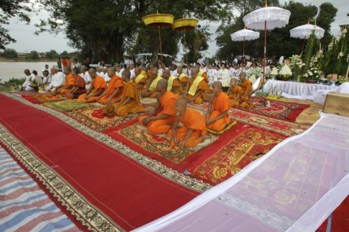 Buddhist monks and their followers sit during the Buddhist ceremony pray before they search for missing Buddha statues in the Tonle Sap river