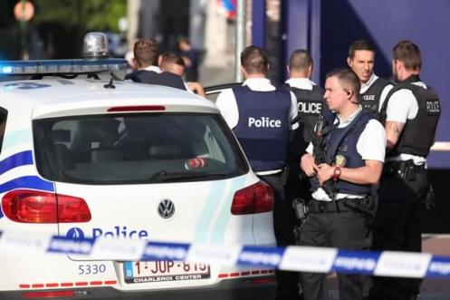 Police stand as they secure the area around a police building in the southern Belgian city