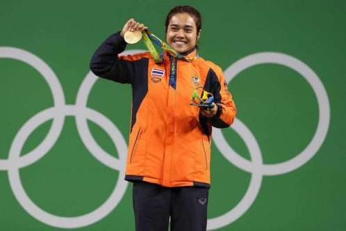 Sopita Tanasan of Thailand holds up her gold medal for the women's 48kg category of weight lifting.