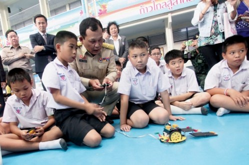 Education Minister General Dapong Ratanasuwan remotely controls a learning toy as he joins students at the Anubarn Pathum Thani School during their after-class activities.