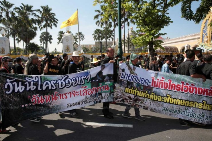 Black-clad farmers holding banners identifying themselves as sugarcane farmers from Surin join the rally against the ban on three farm chemicals, at Government House in Bangkok