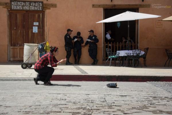 Perita hace una fotografía del espejo de la camioneta, al fondo unos policías leen junto al carro de limpieza de la mujer fallecida.