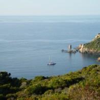 Une petite crique où se trouvent deux bateaux et un rocher bizarre