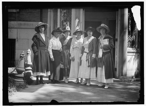 Group of six suffragist women stand outside