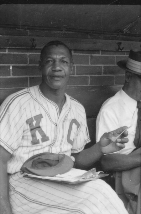 Buck O'Neil of the Kansas City Monarchs in the visitors' dugout, Chicago, August 2, 1955. CHM, ICHi-052256-A; photograph by Arthur Siegel