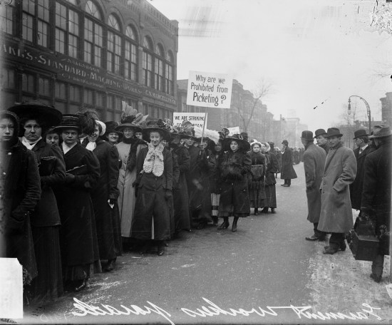 """Image of a parade of women during the garment workers' strike in Chicago. Some women are carrying signs, and one sign reads: """"Why are we prohibited from picketing?"""""""