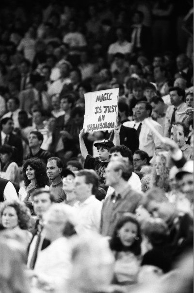 """A young Bulls fan in the crowd holds a sign that reads """"Magic is just an illusion"""""""