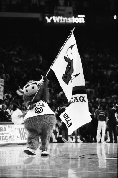 Bulls mascot waves a Bulls flag on the court during a timeout