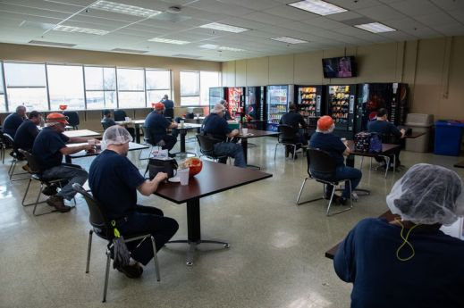 Workers practice social distancing during lunch break at Kraft Foods manufacturing plant in Champaign on March 27.