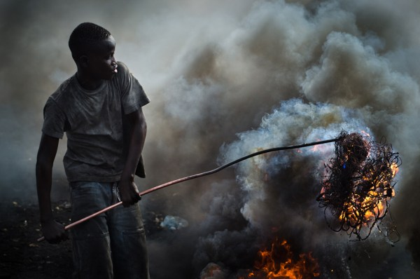 Fifteen-year-old Santana Alhassan Suidu burns a bundle of cords to expose the precious copper wires inside in the Ghanaian slum of Agbogbloshie. Photo by Michael Ciaglo