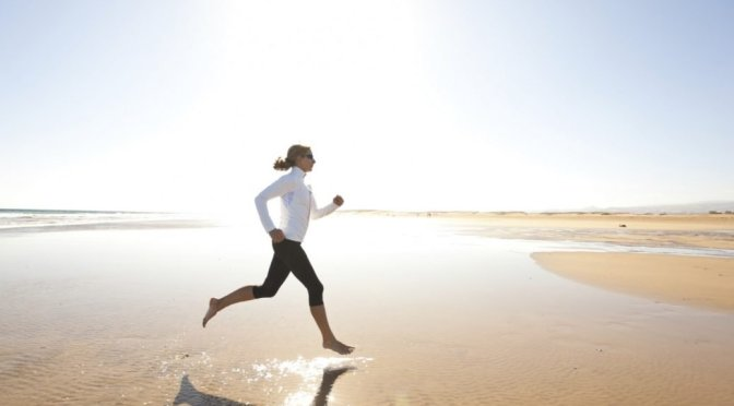 jogging workout on wide sandy beach