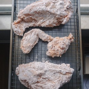 Pale white, flour coated chicken pieces on a cooling rack