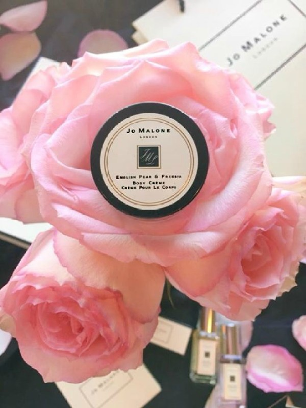 A pink rose with a Jo Malone sample on top of it.