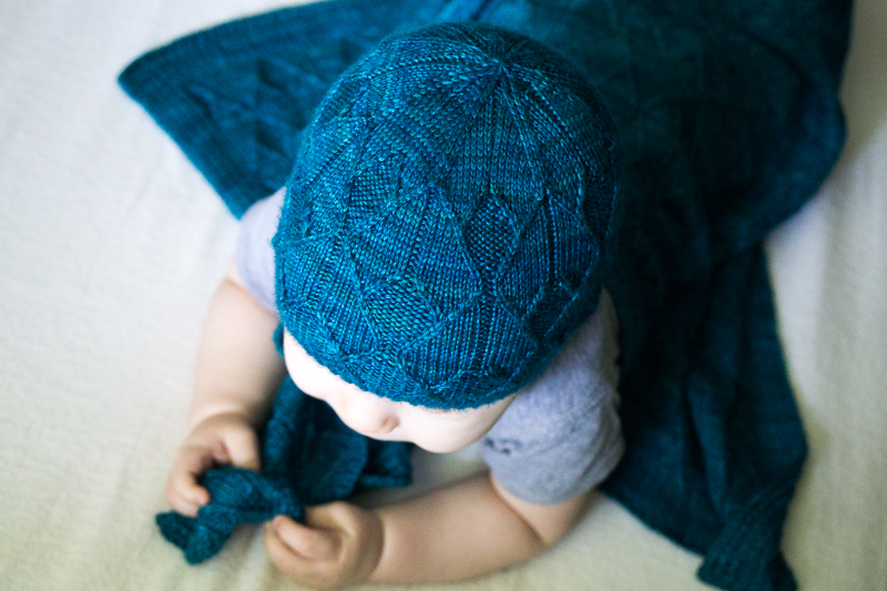 Baby wearing blue Sérac hat and blanket