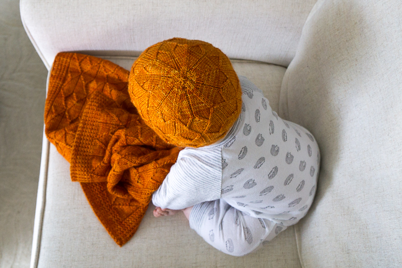 Baby wearing orange Sérac hat and blanket