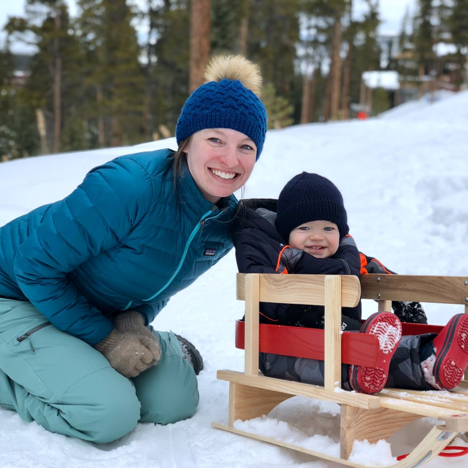 Mother and son in the snow with a sled wearing knitted hats
