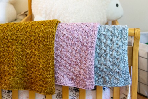 Astrophil blankets in 3 yarn weights shown in yellow, pink and blue