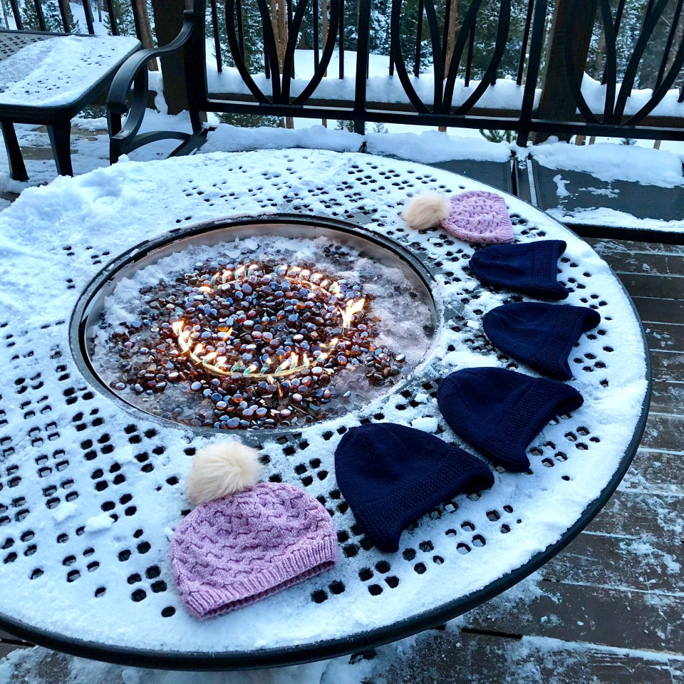 Children's hats lined up around a snowy outdoor fire pit